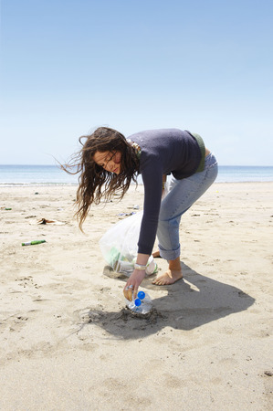 struggled: Young girl collecting garbage on beach