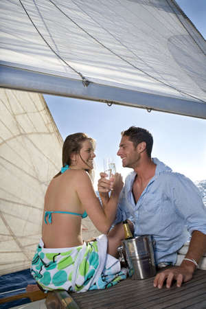 passions: Couple drinking champagne on sailboat