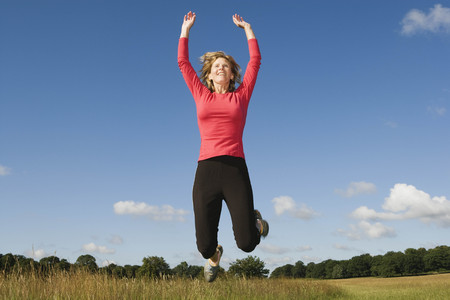 low spirited: Woman jumping in field