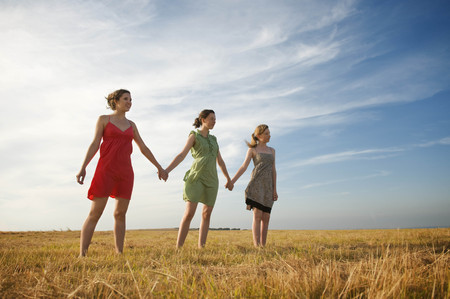 remoteness: Three teenage girls hold hands