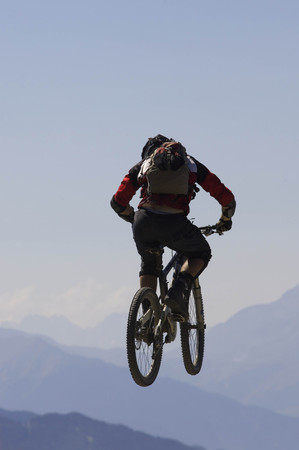 jeopardizing: Mountain biker jumping into the air