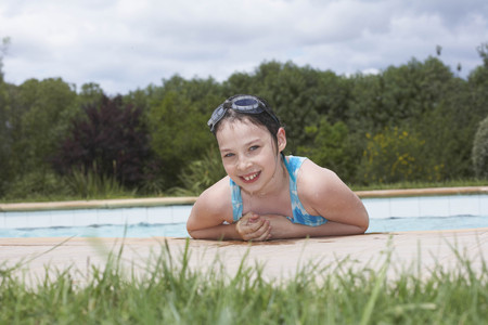 sopping: Young girl smiling by swimming pool LANG_EVOIMAGES