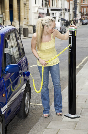 plugging: Young woman charging electric car
