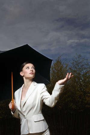 drizzling rain: Woman under an umbrella LANG_EVOIMAGES