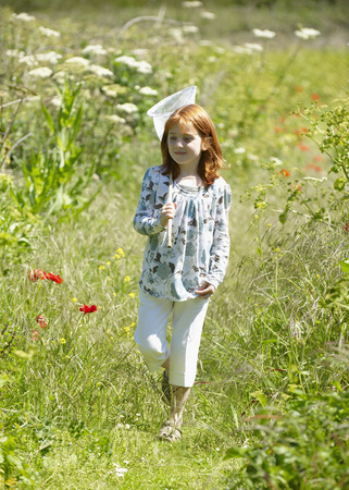 Young girl in field with butterfly net