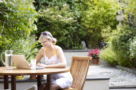 advances: Young woman at garden table on laptop