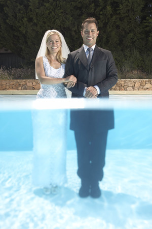 in twos: Wedding couple standing in pool
