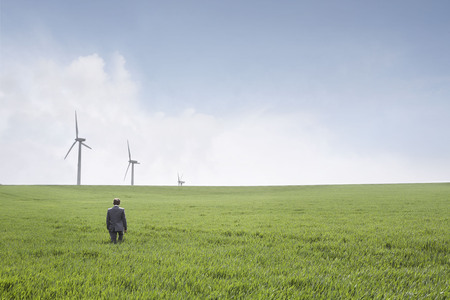 liable: Man walking towards wind turbines LANG_EVOIMAGES