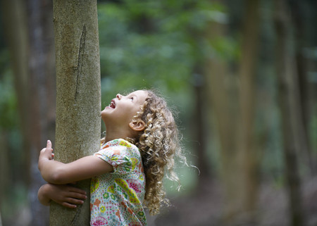 Young girl hugging tree looking up LANG_EVOIMAGES