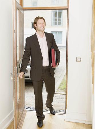 verticals: Business man arrives home