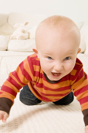 studied: An excited baby crawling to camera.