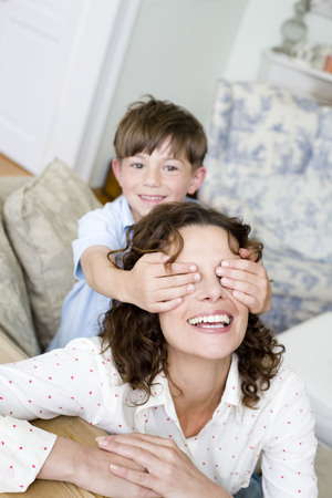 rejoices: Boy holding the eyes of his mum closed LANG_EVOIMAGES