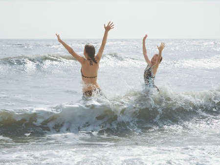 sopping: Girls jumping in the sea