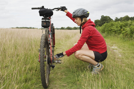 women's issues: Woman cyclist fixing bicycle