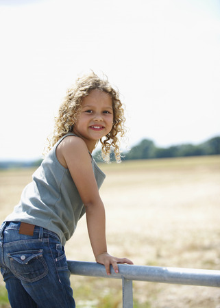 winchester: Young girl on farm gate LANG_EVOIMAGES