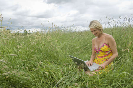 tetbury: Woman sitting in field with laptop LANG_EVOIMAGES