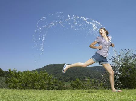 rejuvenated: Girl running through arc of water