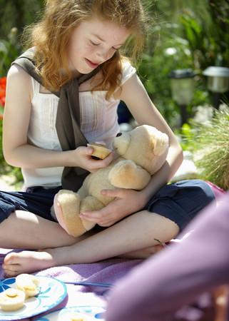 pretending: Girl feeding teddy bear cake LANG_EVOIMAGES