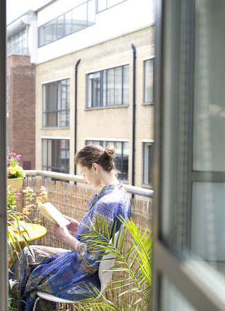 abodes: Woman sitting on balcony reading book