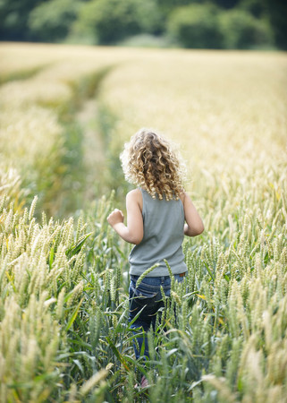 winchester: Young girl walking path in cornfield