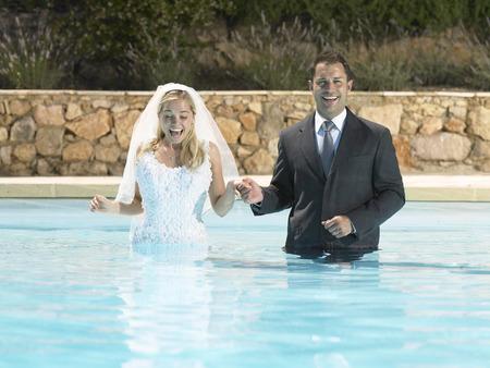 honeymooner: Bride and groom standing in pool LANG_EVOIMAGES