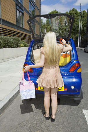 chic woman: Young woman loading electric car