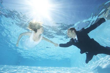 Bride and groom together in pool