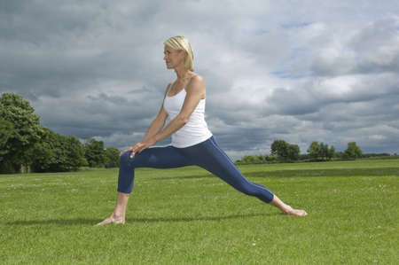 tetbury: Woman in park stretching LANG_EVOIMAGES