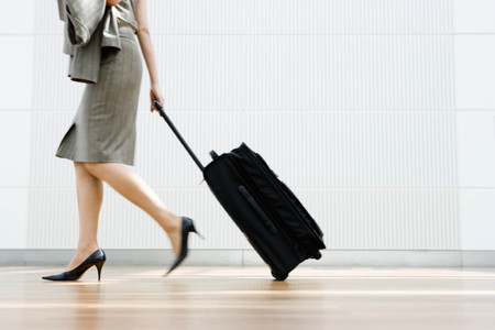 tardiness: Woman dragging a suitcase LANG_EVOIMAGES