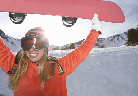 fulfill: Girl lifting ski board, smiling
