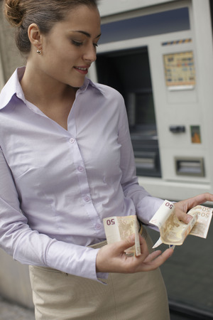 withdrawing: Business woman withdrawing cash LANG_EVOIMAGES