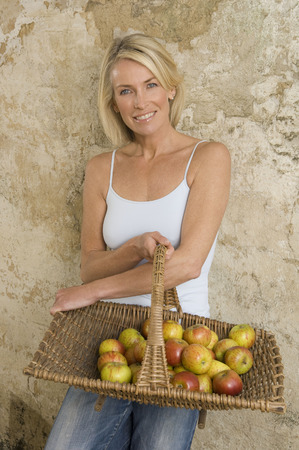 new age: Woman holding basket of apples in barn