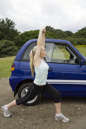 accountable: Young woman exercising by electric car LANG_EVOIMAGES