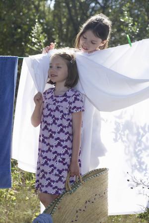dangling: Young girls standing by washing line