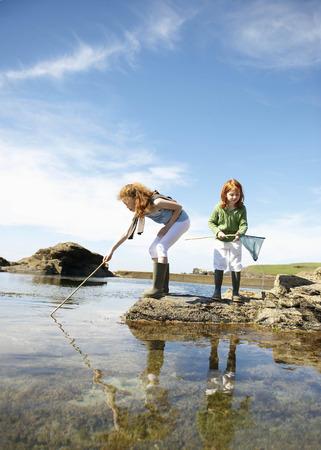 2 girls fishing in rock pool