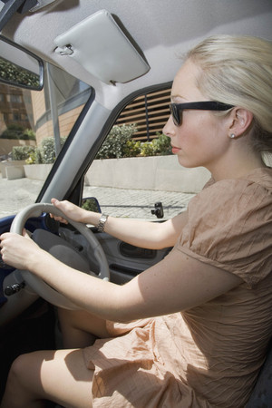 accurately: Young woman driving electric car
