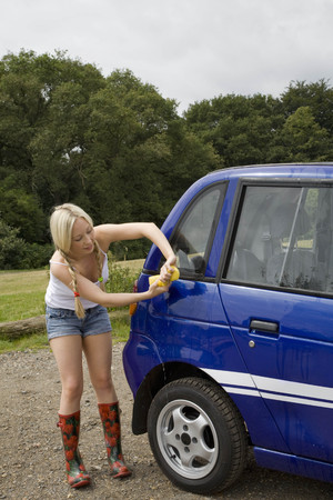 Young woman washing electric car LANG_EVOIMAGES