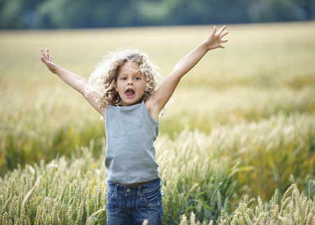 advances: Young girl jumping out of cornfield