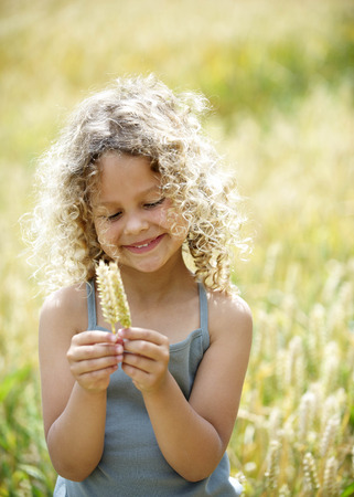 mischeif: Young girl with ears of corn in field LANG_EVOIMAGES