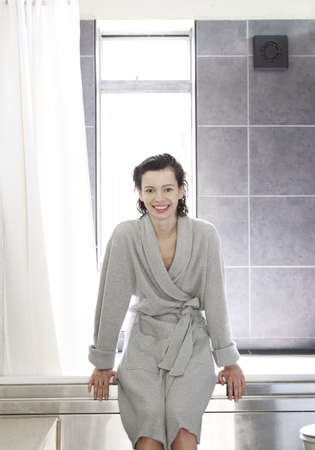 grooming: Woman in bathrobe sitting by bathtub
