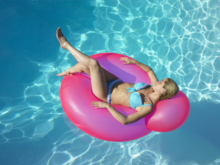 tans: Woman on inflatable chair in pool LANG_EVOIMAGES
