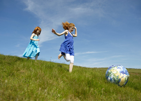 pursuing: 2 young girls running with ball (globe)