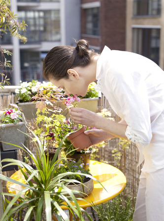 Woman on balcony smelling flowers