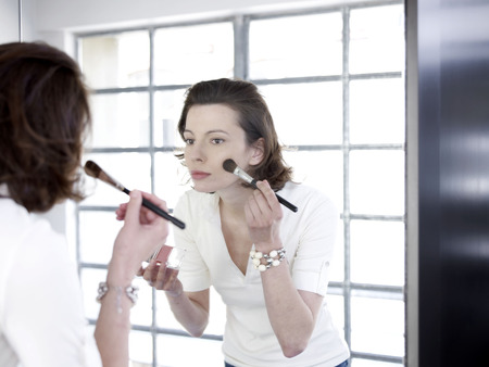 grooming: Woman in mirror applying make up