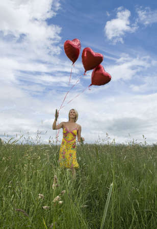 tetbury: Smiling woman in field with balloons LANG_EVOIMAGES