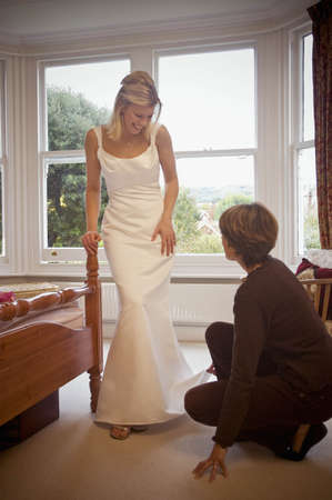 chic woman: A bride having her dress fitted LANG_EVOIMAGES