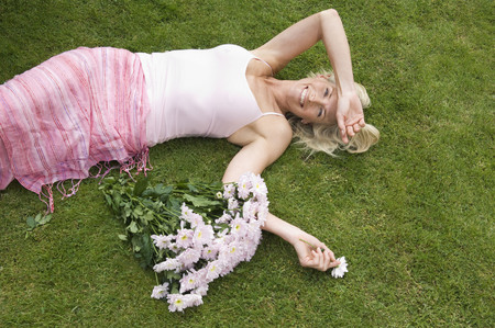tetbury: Relaxed woman lying on grass LANG_EVOIMAGES