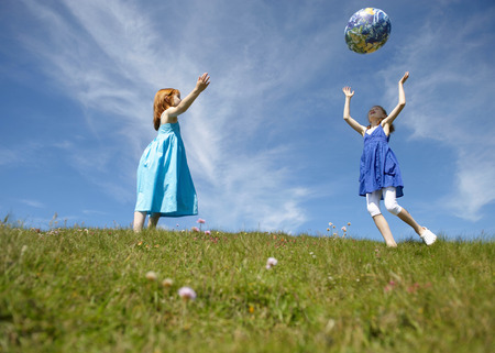 joyous: 2 young girls throwing inflatable globe