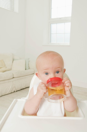 protects: A portrait of a baby drinking juice. LANG_EVOIMAGES