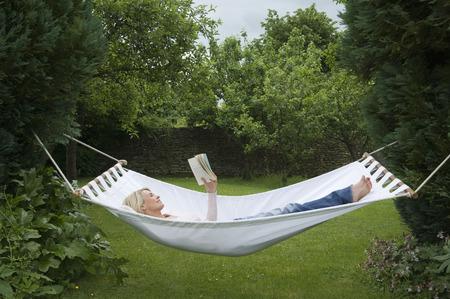 tetbury: Woman relaxing in hammock in garden